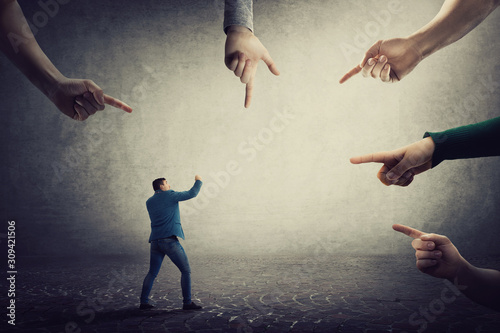 Fototapeta Frustrated businessman starts fighting against people blaming him. Self defense concept, guy fight for truth and justice, being under pressure as multiple index fingers pointing to him. obraz