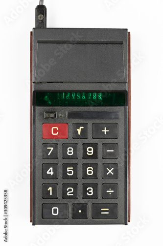 old Soviet calculator with luminous green LEDs numbers on a white background, view from the top - 309425358