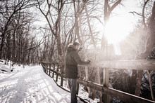 A Man On A Snow Covered Trail Staring Over A Fence Down A Ravine In Matthiessen State Park, LaSalle County, Illinois.