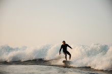 Surfer In Black Swimsuit Rides...