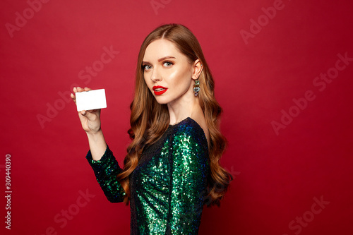 Fototapeta beautiful red-haired model stands on a red background and smiles a beautiful smile in brilliant dress, a card in hands , merry christmas and happy new year	 obraz na płótnie