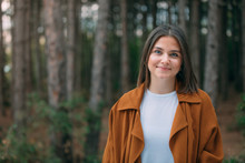 Portrait Of A Young Woman In The Forest. Smiling Girl In Nature Among Green Trees.