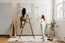 Two Women Painting A Backdrop ...
