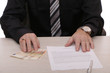 A businessman signs a contract and gives out cash.