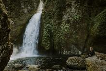 Woman Resting Near Waterfall