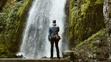 Backside Of Man Looking At A Big Waterfall