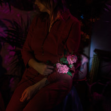 Woman Holds Flower In Lap