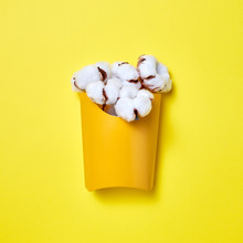 Cotton Flowers In An Orange Cardboard Box On A Yellow Background With Copy Space. Flat Lay