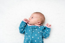A Newborn Baby Laying On A Bed With A Polka Dot Jammies