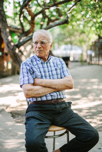 Aged Man Sitting On Chair In C...