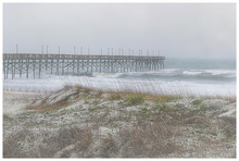Large Waves Washing Up On A Beach Near A Fishing Pier On A Foggy Day