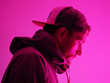 canvas print picture - Head down. profile view. Neon light portrait of serious man in hoody. Bright colorful light effects.
