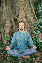 Male Meditating Under Old Tree
