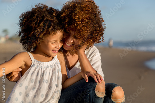 Mother and daughter enjoying a sunny day at the beach - 309465565