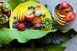 Tropical and colorful fruits, sliced on yellow platter