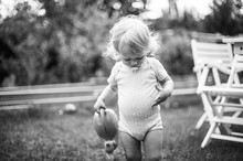A Little Girl Watering The Grass