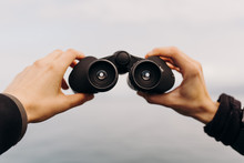 Details Of Hands Holding Binoculars Looking Out Toward Ocean