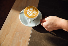 Hand Pushes A Fresh Latte To T...