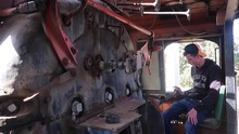 Teenage Boy In Cab Of Disused Locomotive Train Operates Large Lever, Wide Shot