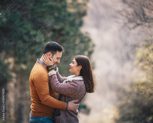 Fotomural Beautiful young couple embracing and caressing on a path through forest