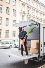 Mover Unloading Potted Plant From Delivery Van On Street In City