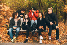 Friends Looking At Teenage Girl Using Mobile Phone While Sitting On Bench At Park