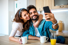 Young Good-looking Caucasian Couple Taking Selfie While They Are Having A Cup Of Coffee In The Kitchen.