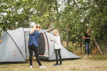 Siblings Preparing Tent In Forest At Camping Site