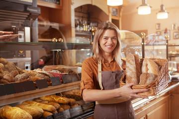 Sretna zrela pekarica koja drži košaru kruha, radi u svojoj pekarnici. Sredovječna poduzetnica koja prodaje domaći kruh