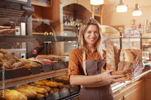 Fototapeta Happy mature female baker holding basket of bread, working at her bakery store. Middle aged female entrepreneur selling homemade bread obraz