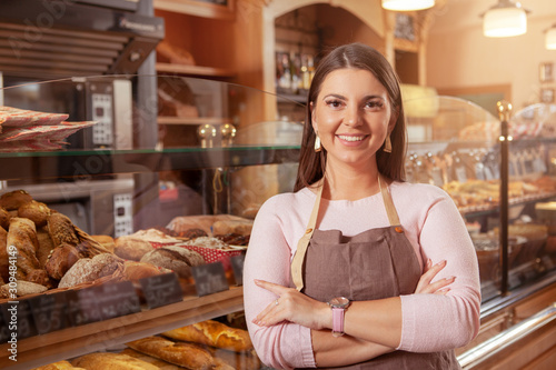 Fototapeta Cheerful female entrepreneur smiling confidently to the camera, working at her bakery store obraz