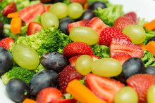 Closeup Of Fruit Salad With Broccoli, Green And Black Grapes, Strawberry Slices And Sliced carrots And Cubes. Delicious, Nutritious And Healthy Meal In White Ceramic Serving Dish On The Wooden Table