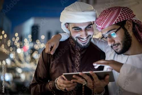 Two Arab men with tablet in city at night Fototapet