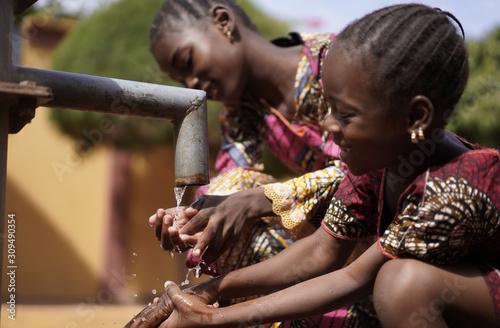 Cuadros en Lienzo Two Gorgeous African Children Girls Drinking Freshwater in Bamako, Mali