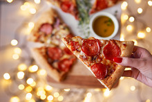 Christmas And New Year Atmosphere.Womans Hand Takes Slice Of Italian Pizza With Melting Tomato, Pepperoni And Cheese On A White Marbel Cutting Board.Background With Lights In Bokeh And Selective Focus