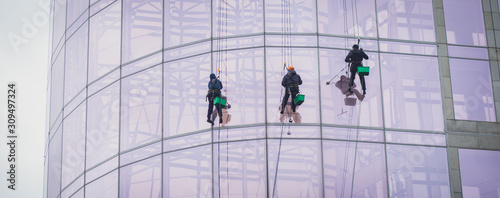 Fototapeta Group of workers cleaning the windows on the high rise building, industrial mountaineers washing the glass facade of a modern office building obraz