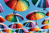 Fototapeta Tęcza - Umbrellas in rainbow color on blue sky background