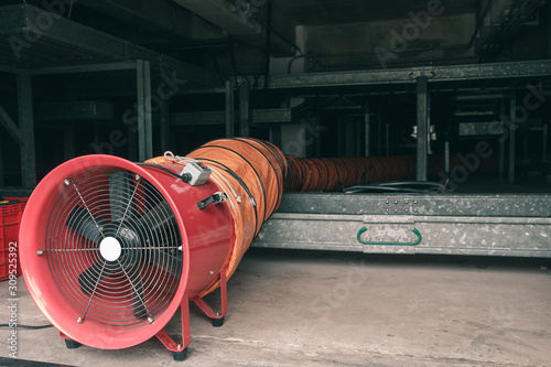 Photo Red blower flow air for confined space work in factory
