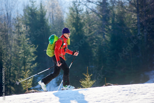 Fototapeta Happy sportive male skier tourist with backpack in sunglasses walking on skis uphill in deep snow on background of winter wood on sunny cold day