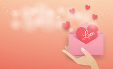 Hand Holding A Pink Envelope With A Dark Red Heart Floating Out Of The Envelope With A White Spray On The Pink Background