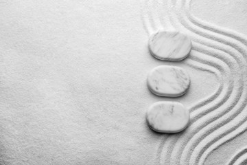 Top view of white stones on sand with pattern, space for text. Zen, meditation, harmony