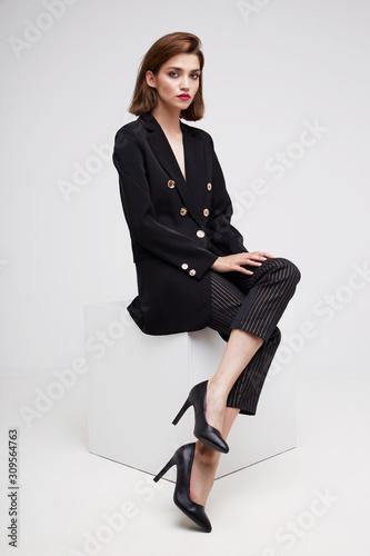 High fashion portrait of young elegant woman. Black jacket, pants. Wall mural
