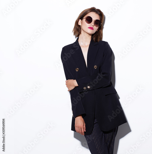 High fashion portrait of young elegant woman. Sunglasses, black jacket, pants. Wall mural