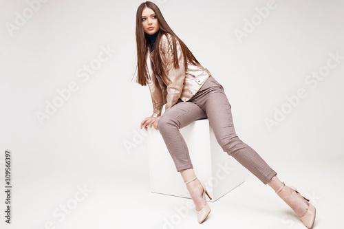 Obraz Fashion model in golden leather jacket posing in studio. - fototapety do salonu