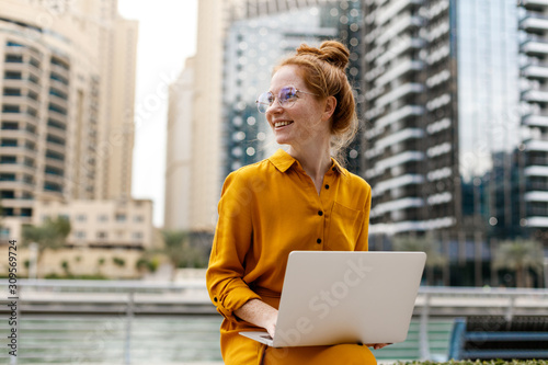 Young Woman sitting in Dubai Marina aria and work on laptop Wallpaper Mural