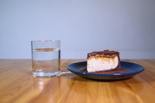 Snickers Cheesecake On A Blue Saucer And A Glass Of Water On A Large Bright Wooden Table