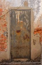 Closeup Neglected Vintage Rusty Steel Door With Wooden Doorframe On Brick Wall With Cement Plaster