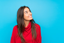 Young Woman With Red Sweater Over Isolated Blue Background Laughing And Looking Up