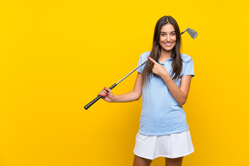 Young golfer woman over isolated yellow wall pointing to the side to present ...