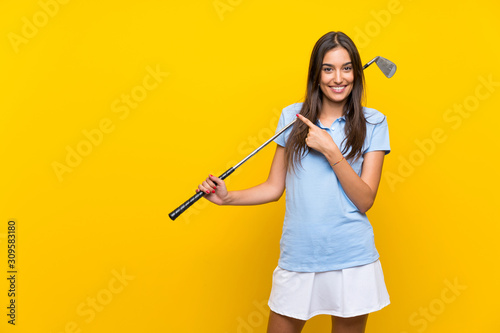 Young golfer woman over isolated yellow wall pointing to the side to present a p Fototapete